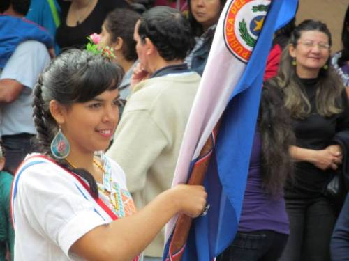 A school girl carries the Paraguayan flag in a parade. Students with the highest grades were flag bearers.